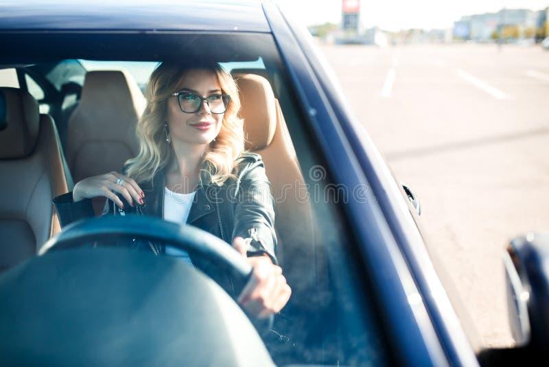 Imagen de la mujer joven con los vidrios que conducen el coche negro foto de archivo