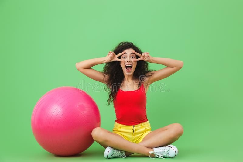 Imagen de la mujer joven que se sienta en piso con la bola de la aptitud durante aeróbicos contra la pared verde imagen de archivo