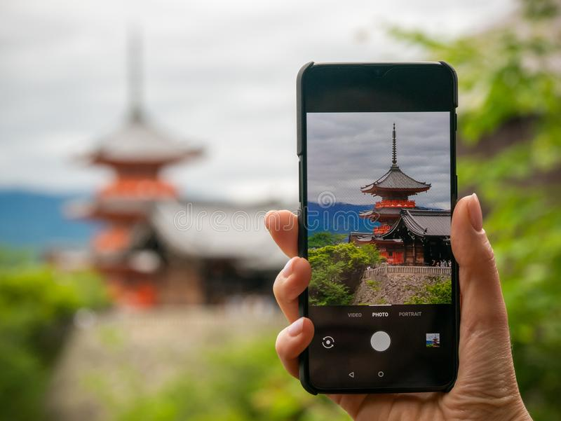 Imagen de la mujer joven que sostiene el tel?fono m?vil con el templo de madera antiguo en la pantalla, con colores del follaje d imagen de archivo