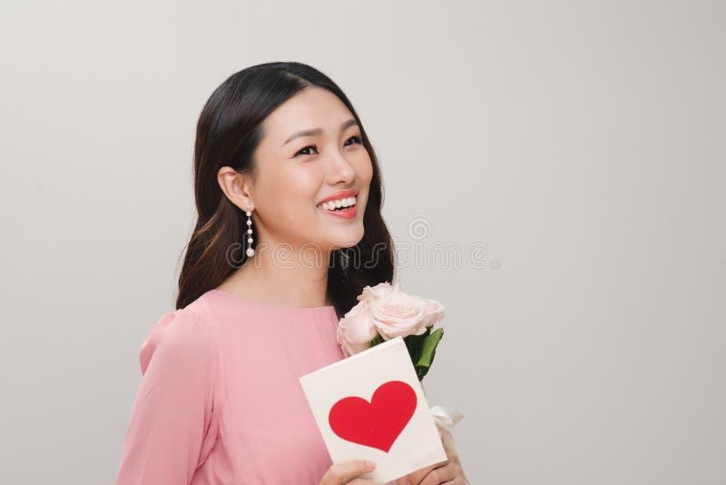 Imagen de la mujer joven que sostiene la flor y la postal imágenes de archivo libres de regalías