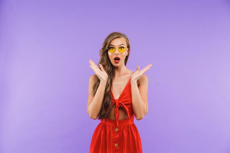 Imagen de la mujer morena 20s de la moda que lleva el vestido y el sungla rojos imagenes de archivo