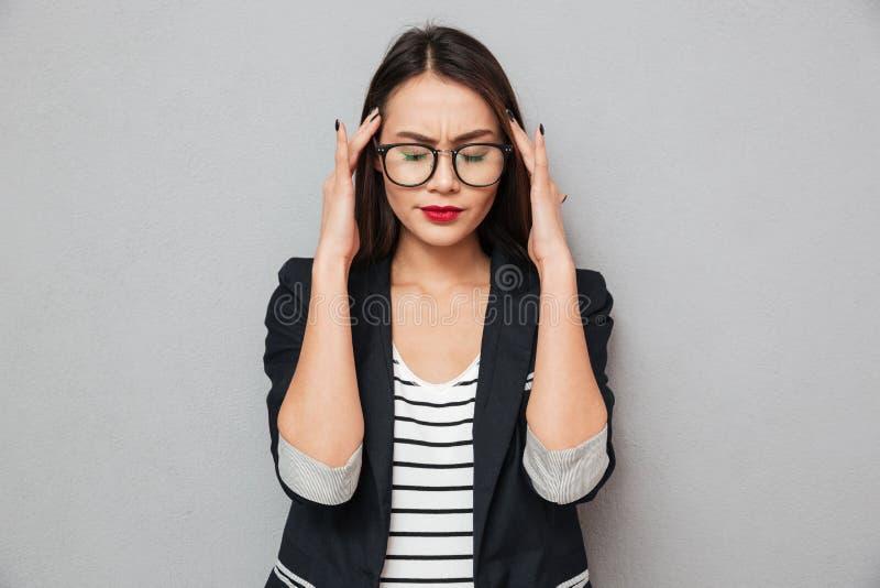 Imagen de la mujer de negocios asiática confusa en las lentes que tienen dolor de cabeza imagenes de archivo