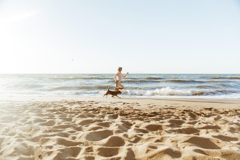 Imagen de la mujer positiva en sombrero de paja, corriendo con su perro marrón a lo largo de la costa fotos de archivo