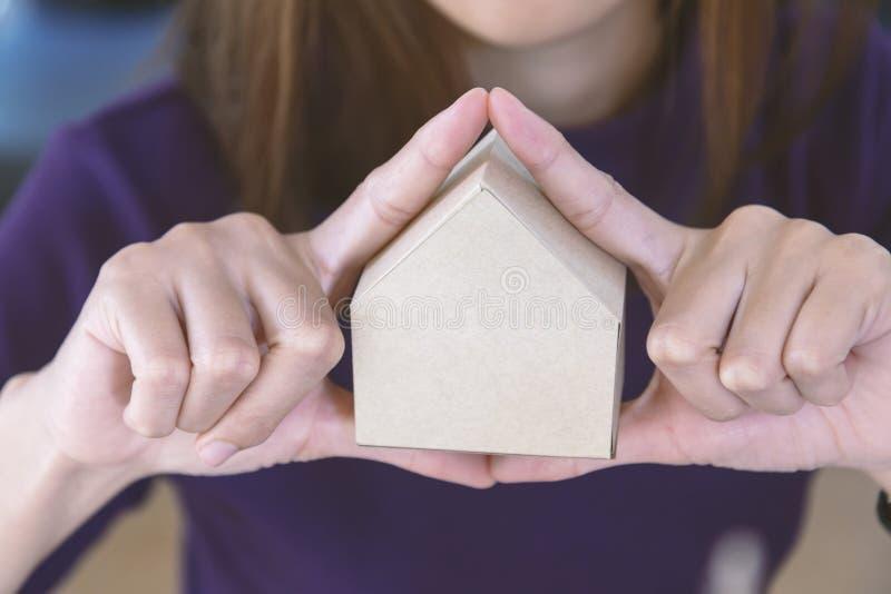 Imagen de la mujer que lleva a cabo el modelo de papel de la casa en sus manos fotos de archivo