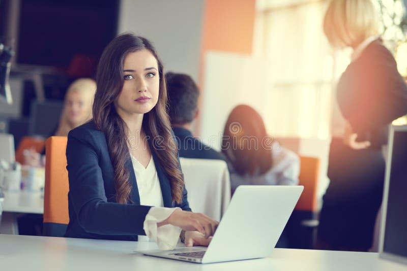 Imagen de la mujer que usa el ordenador portátil mientras que se sienta en su escritorio fotografía de archivo