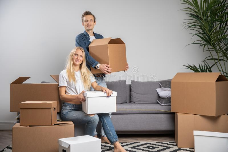 Imagen de la mujer y del hombre felices entre las cajas de cartón i fotografía de archivo libre de regalías
