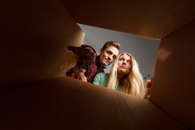 Imagen de la mujer y del hombre que miran dentro de la caja de cartón fotografía de archivo