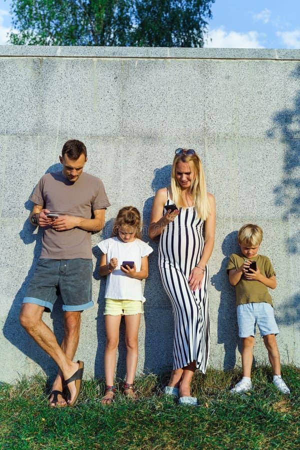 Imagen de la mujer y hombre y niños rubios con los teléfonos en sus manos que se colocan en el muro de cemento en la calle fotografía de archivo