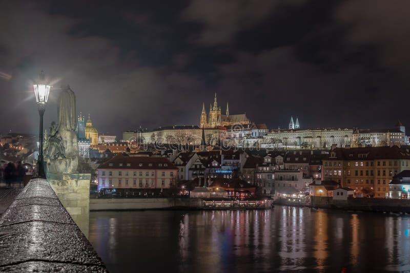 Imagen de la noche del castillo de Praga del puente de Charles con el río en el primero plano fotos de archivo libres de regalías