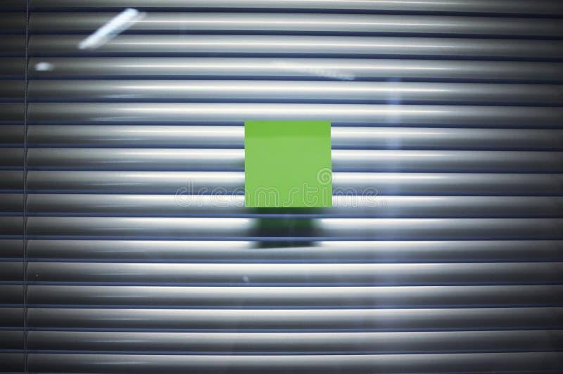 Imagen de la nota pegajosa en blanco sobre la pared de cristal de la oficina con la persiana imagenes de archivo