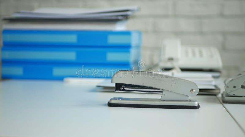Imagen de la oficina del escritorio con documentos archivados y una grapadora usada para sujetar con grapa de papel foto de archivo