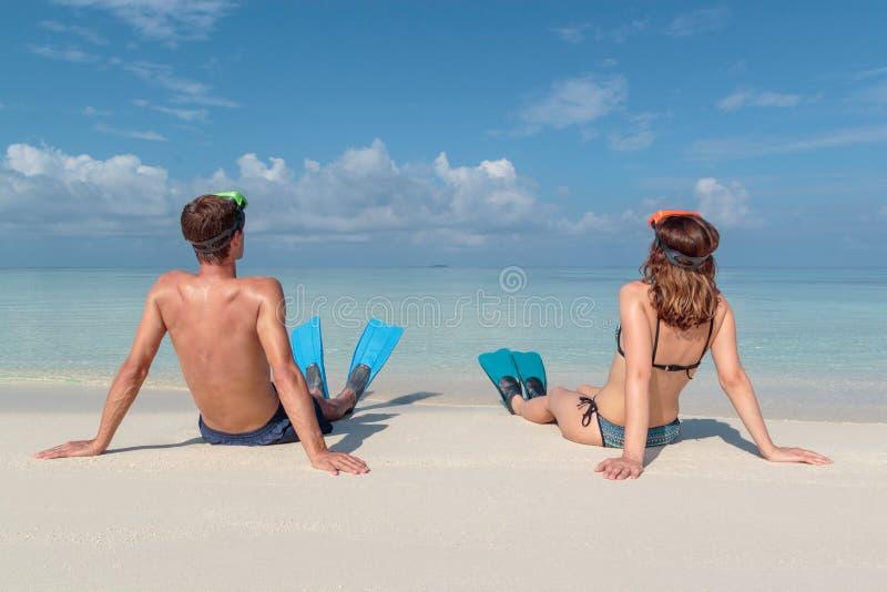 Imagen de la parte posterior de un par joven con las aletas y de la máscara asentada en una playa blanca en los Maldivas Agua azu imágenes de archivo libres de regalías