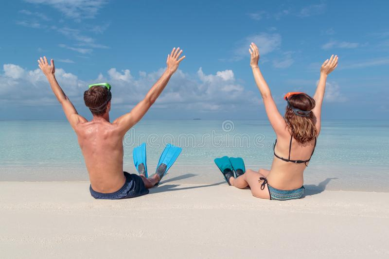 Imagen de la parte posterior de un par joven con las aletas y de la m?scara asentada en una playa blanca en los Maldivas Agua azu fotos de archivo libres de regalías