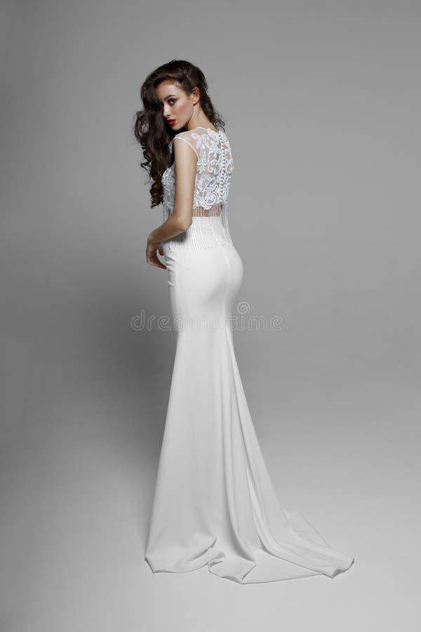 Imagen de la parte posterior una señora espléndida en el vestido largo blanco con la franja, aislada en un fondo blanco imagenes de archivo