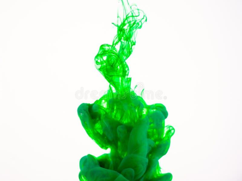 Imagen de la pintura verde que disuelve en el agua La foto de Deteiled de la pintura verde cayó en el líquido, fondo abstracto imagenes de archivo