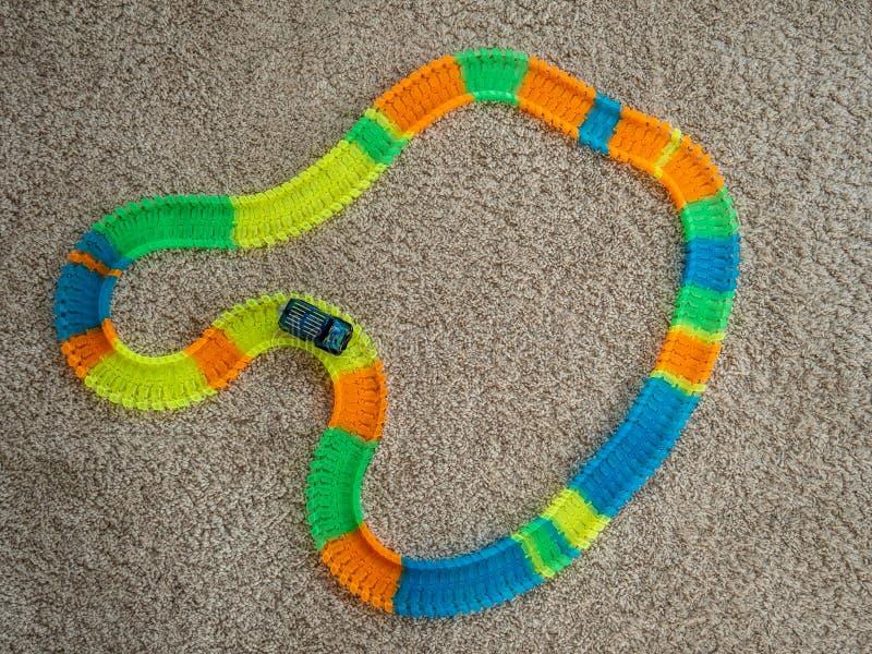 Imagen de la pista del coche del juguete con el coche y de los elementos coloridos de la pista en la alfombra fotografía de archivo
