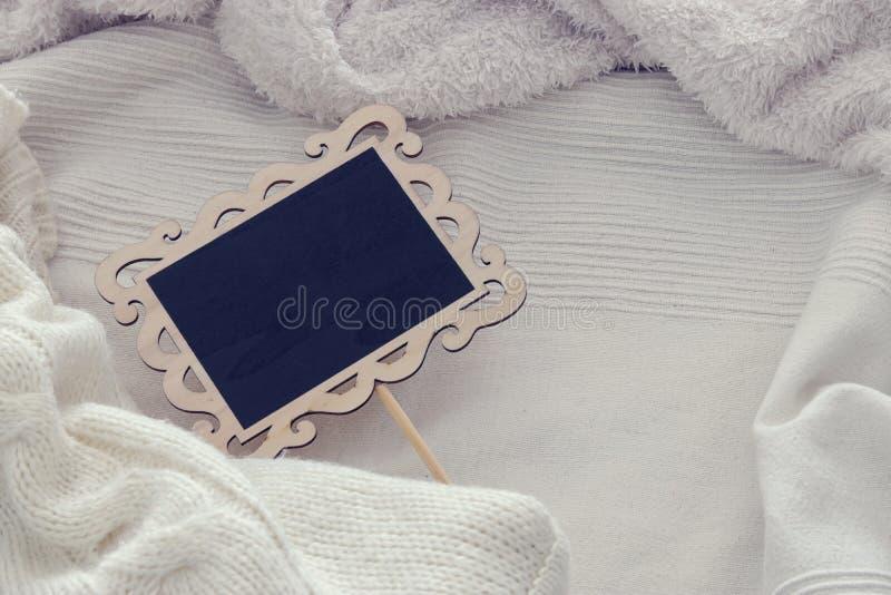 Imagen de la pizarra vacía sobre la manta acogedora y blanca Visión superior foto de archivo