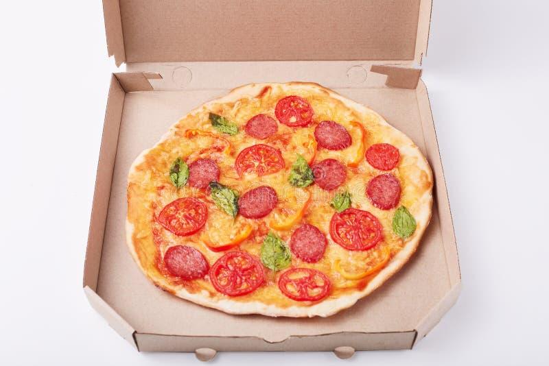 Imagen de la pizza sabrosa fresca en caja de cartón en la superficie blanca, imagen del plato de los alimentos de preparación ráp imagen de archivo