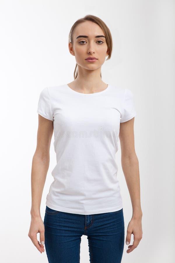 Imagen de la plantilla de la camiseta blanca que lleva de la chica joven con el lugar para el texto y tejanos, espacio de la copi imagen de archivo