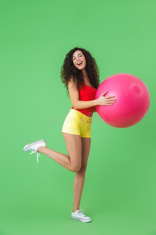 Imagen de la ropa activa del verano de la mujer que lleva 20s que hace ejercicios con la bola de la aptitud durante aeróbicos imagenes de archivo