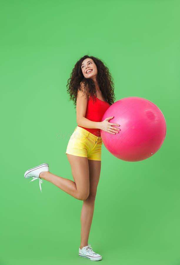 Imagen de la ropa atractiva del verano de la mujer que lleva 20s que hace ejercicios con la bola de la aptitud durante aeróbicos imagen de archivo libre de regalías