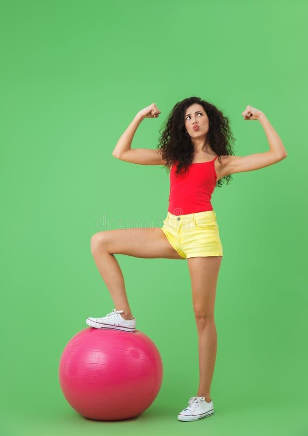 Imagen de la ropa fuerte del verano de la mujer que lleva 20s que hace ejercicios con la bola de la aptitud durante aeróbicos imagen de archivo libre de regalías