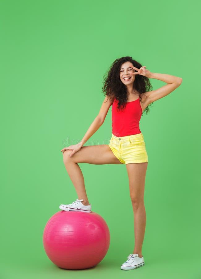 Imagen de la ropa hermosa del verano de la mujer que lleva 20s que hace ejercicios con la bola de la aptitud durante aeróbicos fotografía de archivo libre de regalías