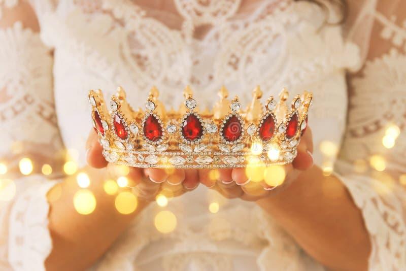 imagen de la señora hermosa con el vestido blanco del cordón que sostiene la corona del diamante período medieval de la fantasía imagenes de archivo