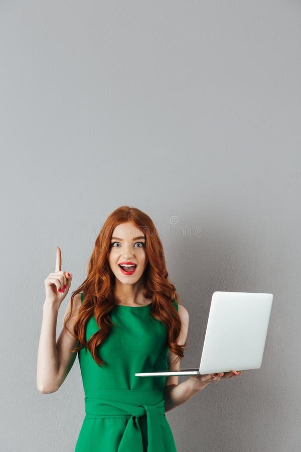 Imagen de la señora joven admirable con el pelo largo rojo que señala el finger imágenes de archivo libres de regalías