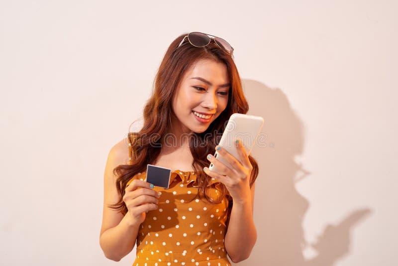 Imagen de la se?ora joven emocionada usando el tel?fono m?vil que sostiene la tarjeta de cr?dito fotos de archivo libres de regalías