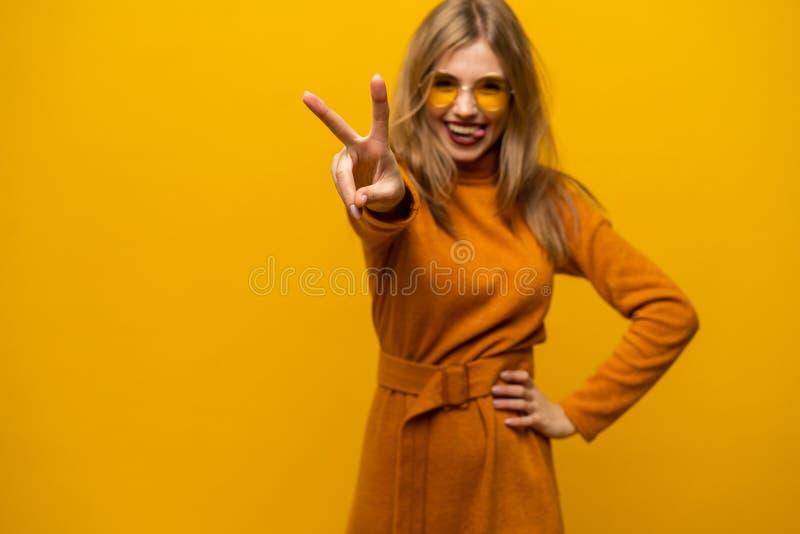 Imagen de la situación feliz de la mujer joven aislada sobre el fondo amarillo que muestra gesto de la paz mirada de la cámara fotografía de archivo
