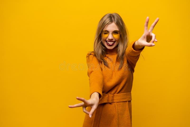 Imagen de la situación feliz de la mujer joven aislada sobre el fondo amarillo que muestra gesto de la paz mirada de la cámara imagenes de archivo