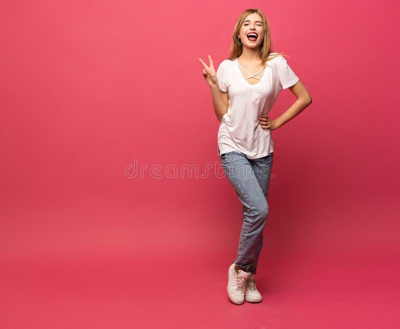 Imagen de la situación feliz de la mujer joven aislada sobre el fondo rosado que muestra gesto de la paz mirada de la cámara fotos de archivo libres de regalías