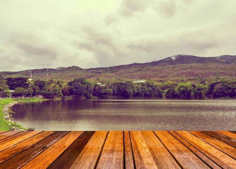 imagen de la tabla de madera vieja con la imagen del lago con la montaña fotografía de archivo