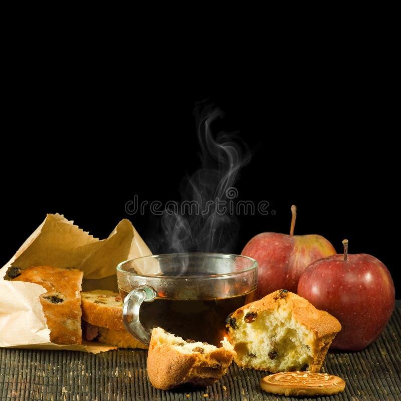 Imagen de la taza de té, de galleta y de manzanas en un fondo negro imagenes de archivo