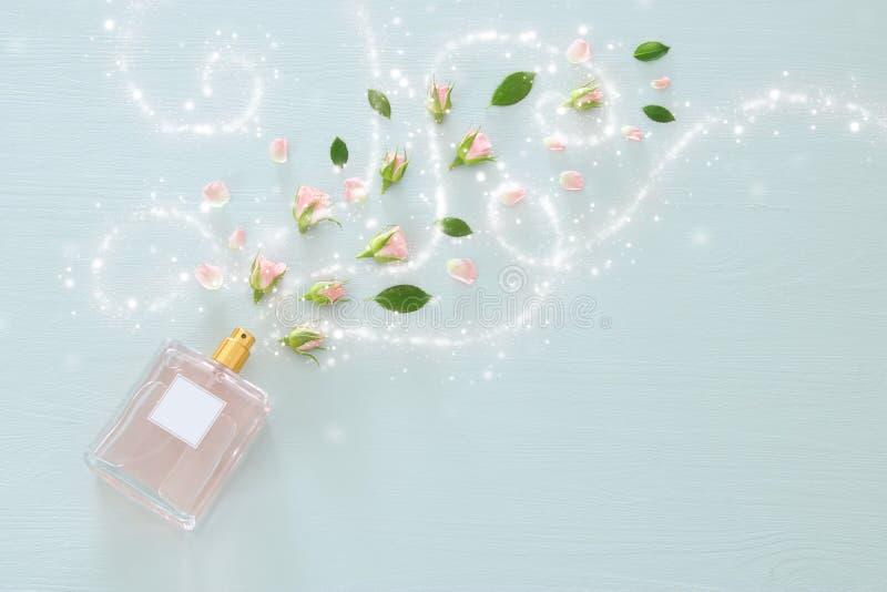 Imagen de la visión superior de la botella de perfume con las flores de los pétalos color de rosa sobre fondo azul en colores pas foto de archivo libre de regalías