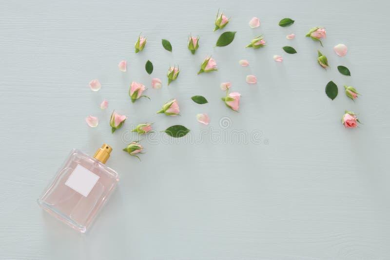 Imagen de la visión superior de la botella de perfume con las flores de los pétalos color de rosa sobre fondo azul en colores pas imagenes de archivo