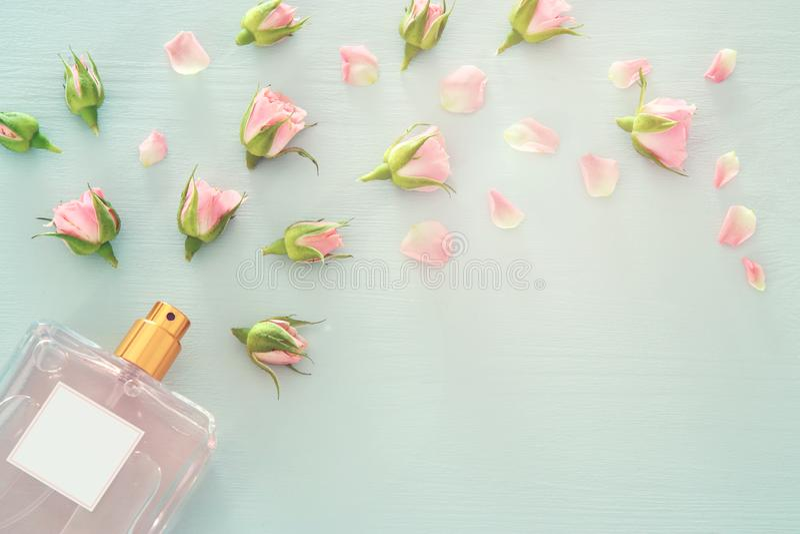 Imagen de la visión superior de la botella de perfume con las flores de los pétalos color de rosa sobre fondo azul en colores pas foto de archivo