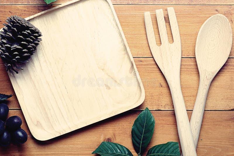 Imagen de la visión superior de la cuchara de madera, de la bifurcación y de la bandeja en blanco colocadas en la tabla de madera fotos de archivo