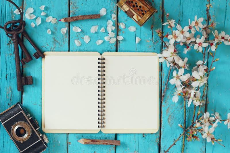 Imagen de la visión superior del árbol blanco de las flores de cerezo de la primavera, cuaderno en blanco abierto, cámara vieja e fotografía de archivo