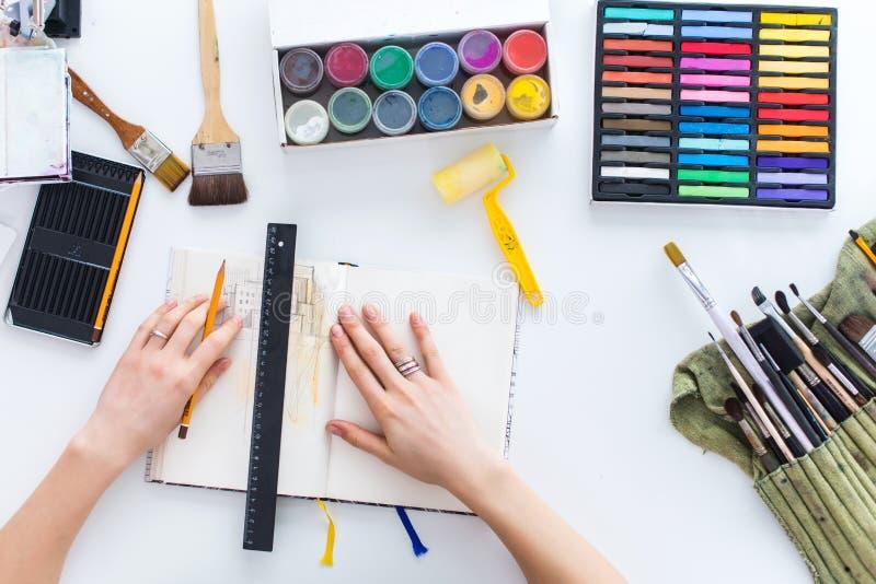 Imagen de la visión superior del bosquejo del dibujo del pintor en sketchbook usando el lápiz, los creyones y las pinturas del ag imagen de archivo libre de regalías