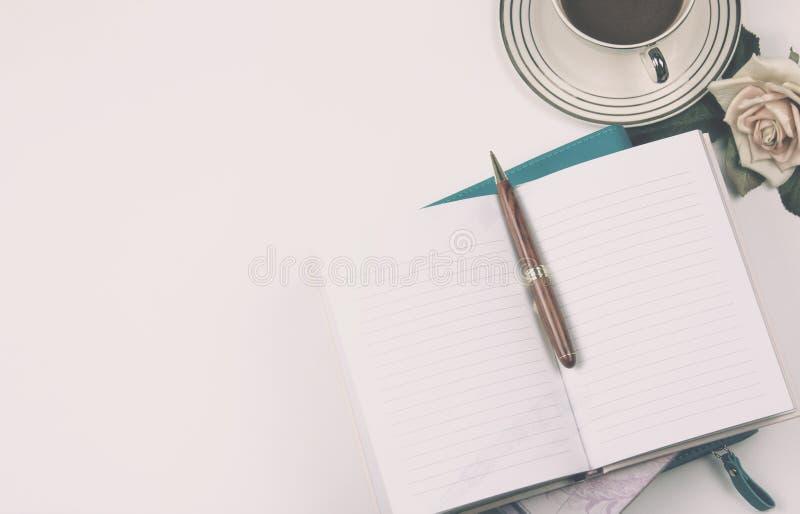 Imagen de la visión superior del cuaderno abierto con las páginas en blanco al lado de la rosa y de la taza de café en el escrito fotos de archivo libres de regalías