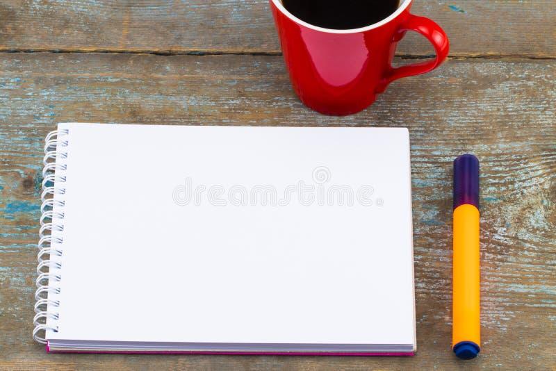 Imagen de la visión superior del cuaderno abierto con las páginas en blanco al lado de la taza de fotografía de archivo