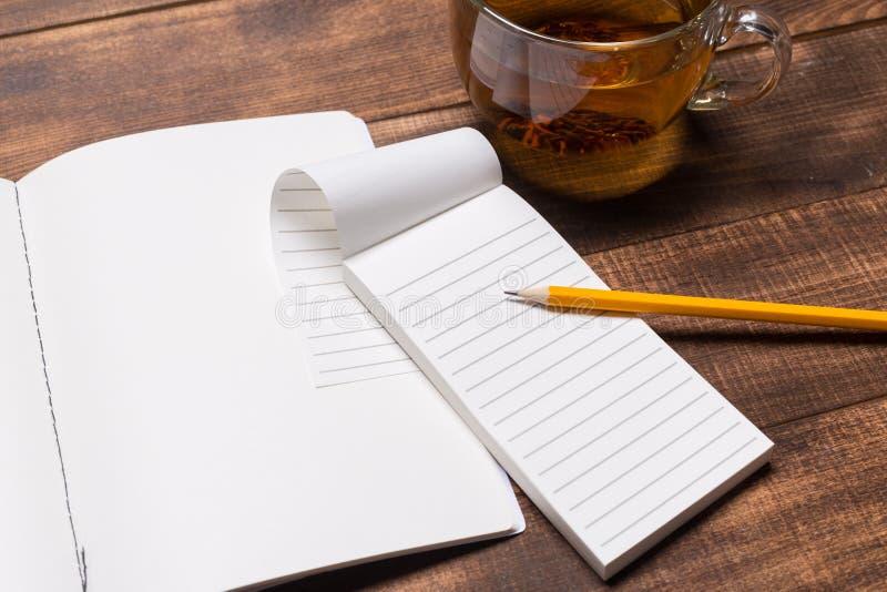 imagen de la visión superior del cuaderno abierto con las páginas en blanco al lado de la taza de café en la tabla de madera Maqu imagenes de archivo