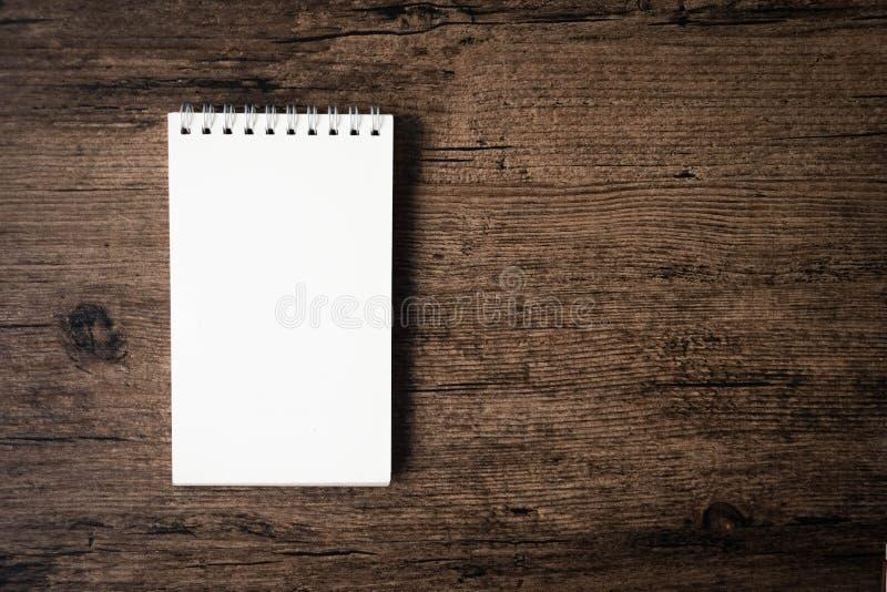 Imagen de la visión superior del cuaderno abierto con la página en blanco en TA de madera fotos de archivo libres de regalías