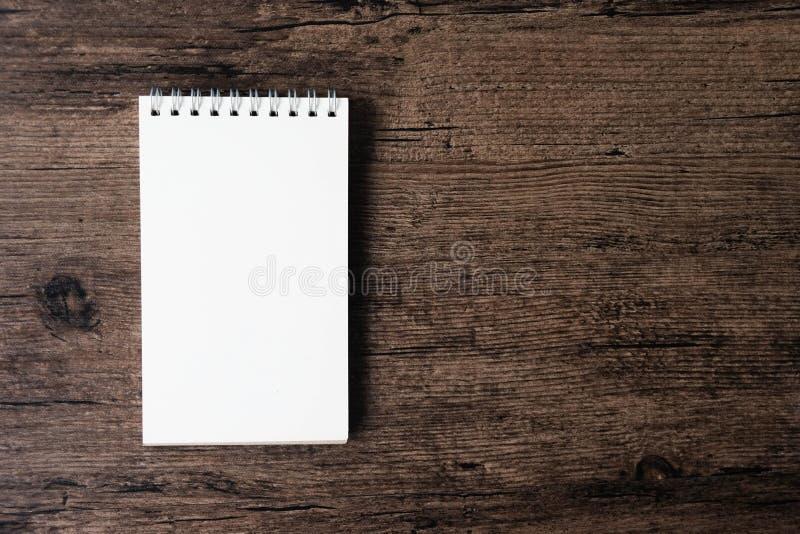 Imagen de la visión superior del cuaderno abierto con la página en blanco en TA de madera imagen de archivo libre de regalías