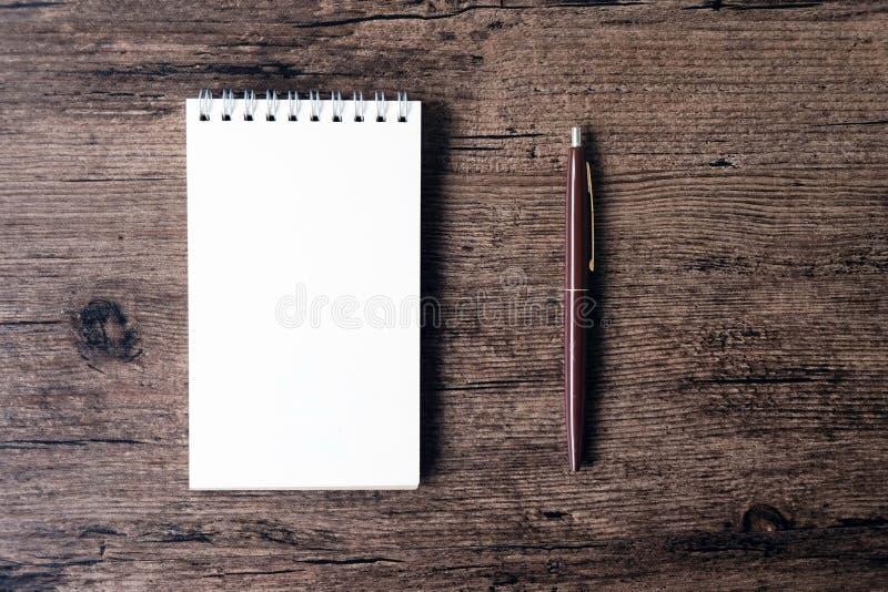 Imagen de la visión superior del cuaderno abierto con la página en blanco y de la pluma en el w imagen de archivo libre de regalías