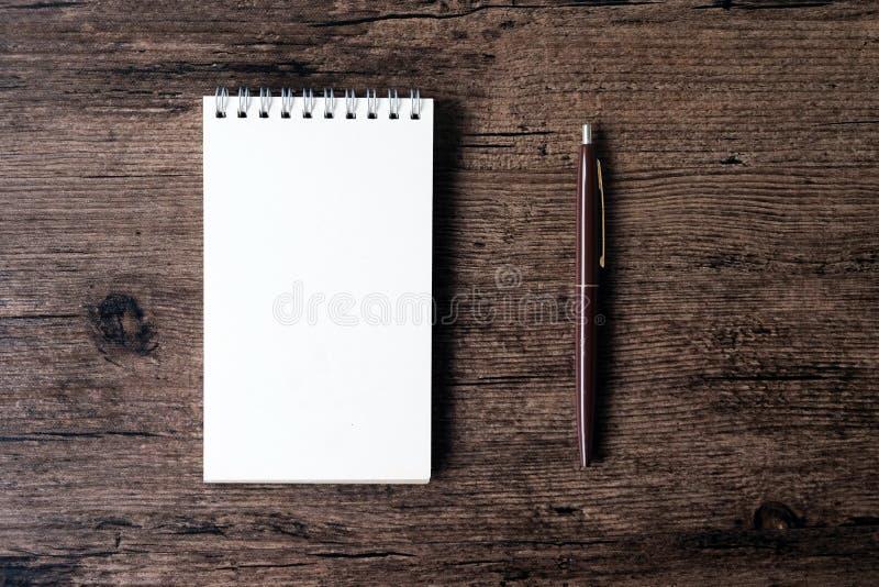 Imagen de la visión superior del cuaderno abierto con la página en blanco y de la pluma en el w imagenes de archivo