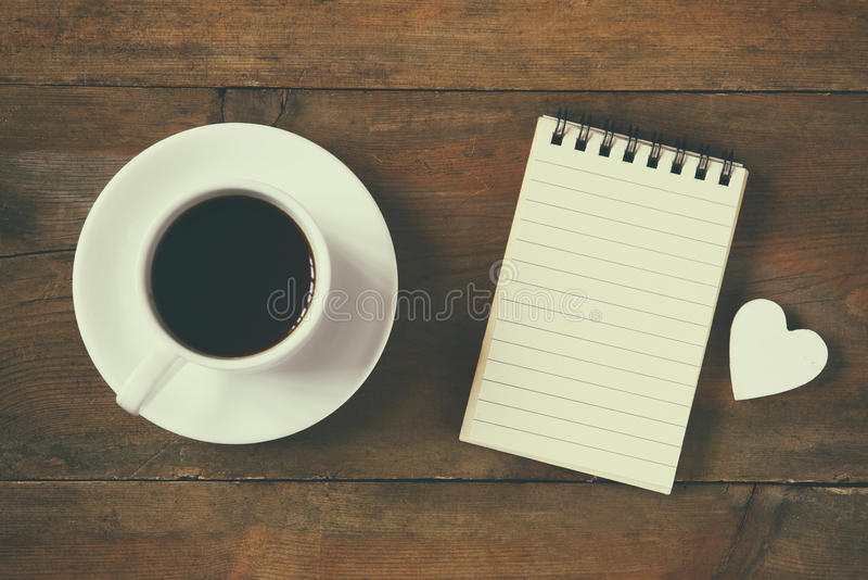 Imagen de la visión superior del cuaderno en blanco al lado de la taza de café vintage filtrado y entonado foto de archivo libre de regalías