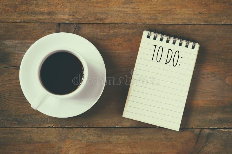 Imagen de la visión superior del cuaderno en blanco con el texto A HACER, al lado de la taza de café en el escritorio de madera v foto de archivo libre de regalías